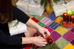 Το κορίτσι συσκευάζει τα δώρα κοντά σε ένα χριστουγεννιάτικο δέντρο Στοκ εικόνες με δικαίωμα ελεύθερης χρήσης