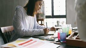 Το κορίτσι σχεδιαστών εργάζεται στον πίνακα Σκίτσα σχεδίων creative process Βιντεοσκοπημένες εικόνες φιλμ μικρού μήκους