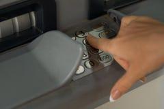 Το κορίτσι σχηματίζει τον κωδικό πρόσβασης στο ATM Στοκ εικόνα με δικαίωμα ελεύθερης χρήσης
