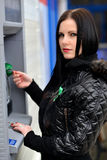 Το κορίτσι σύρει έξω τα χρήματα σε μετρητά ATM Στοκ Εικόνα