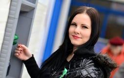 Το κορίτσι σύρει έξω τα χρήματα σε μετρητά ATM Στοκ Εικόνες