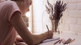 Το κορίτσι σύρει σε ένα σημειωματάριο Στα φω'τα υποβάθρου, καθρέφτης σύνθεσης κόκκινο με την άσπρη ένωση βράδυ απόθεμα βίντεο