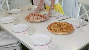 Το κορίτσι τακτοποιεί την πίτσα στον πίνακα απόθεμα βίντεο