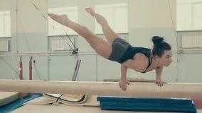 Το κορίτσι της αθλητικής κατασκευής, στη γυμναστική, εκτελεί ένα frieze σε έναν φραγμό, κατόπιν εξετάζει τη κάμερα, σε αργή κίνησ φιλμ μικρού μήκους