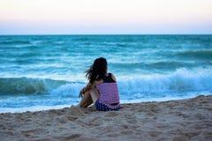 Το κορίτσι της Ασίας κάθεται στην παραλία μόνη Στοκ Φωτογραφία