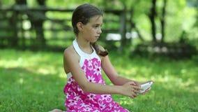 Το κορίτσι της Νίκαιας κάθεται στη χλόη και κάνει τις φωτογραφίες στο smartphone του απόθεμα βίντεο