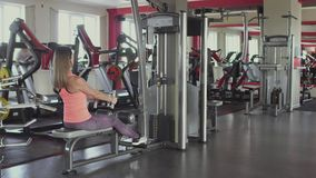 Το κορίτσι τινάζει τους μυς βραχιόνων της στον προσομοιωτή κατάρτισης στη λέσχη γυμναστικής ή ικανότητας Γυναίκα που κάνει τα σωμ φιλμ μικρού μήκους