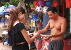 Το κορίτσι τουριστών αγοράζει τα φρούτα στην του χωριού αγορά Στοκ φωτογραφία με δικαίωμα ελεύθερης χρήσης