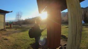 Το κορίτσι τουριστών περιστρέφει μια ρόδα προσευχής δίπλα σε έναν βουδιστικό ναό στην ηλιόλουστη ημέρα απόθεμα βίντεο