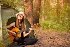 Το κορίτσι τουριστών στο καπέλο κάθεται στη σκηνή και την παίζοντας έννοια κιθάρων Υπόλοιπο τουρισμού στη φύση στοκ εικόνα