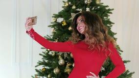 Το κορίτσι του νέου έτους selfie φωτογραφίστηκε στο υπόβαθρο του χριστουγεννιάτικου δέντρου, μια όμορφη γυναίκα σε έναν εορταστικ απόθεμα βίντεο
