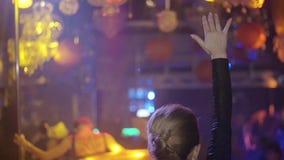 Το κορίτσι του DJ πίσω πλευράς αυξάνει το χέρι στην περιστροφική πλάκα στο νυχτερινό κέντρο διασκέδασης Πηγαίνετε πηγαίνει κορίτσ φιλμ μικρού μήκους