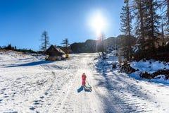 Το κορίτσι τραβά το έλκηθρο χιονιού στο χιονοδρομικό κέντρο που φορά το χειμώνα ντύνει Στοκ Εικόνες