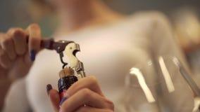 Το κορίτσι τραβά το φελλό από ένα μπουκάλι κρασιού με μια κινηματογράφηση σε πρώτο πλάνο ανοιχτήρι Ένα κορίτσι με ένα όμορφο unco απόθεμα βίντεο