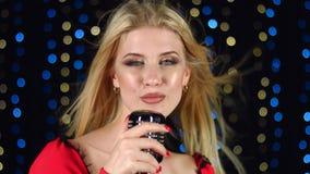 Το κορίτσι τραγουδά τα ενεργητικά τραγούδια στο υπόβαθρο χρωμάτισε τα φω'τα απόθεμα βίντεο