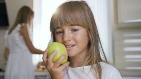Το κορίτσι τρώει ένα μεγάλο πράσινο μήλο Κινηματογράφηση σε πρώτο πλάνο Ένας όμορφος έφηβος τρώει ένα μήλο στο σπίτι στην κουζίνα απόθεμα βίντεο