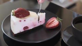Το κορίτσι τρώει το κέικ φρούτων κρέμας, το κέικ και ένα φλυτζάνι του μαύρου καφέ σε έναν μαύρο πίνακα γυαλιού απόθεμα βίντεο