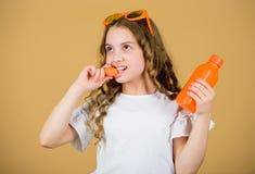 Το κορίτσι τρώει το λαχανικό καρότων και πίνει το χυμό καρότων r μικρό κορίτσι στα γυαλιά μόδας Διατροφή βιταμινών στοκ φωτογραφία με δικαίωμα ελεύθερης χρήσης