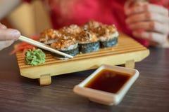 Το κορίτσι τρώει τα ιαπωνικά τρόφιμα κρατά τους ρόλους σουσιών με το ξύλινο chopsti Στοκ εικόνες με δικαίωμα ελεύθερης χρήσης