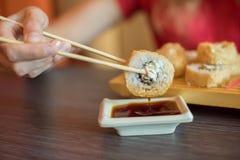 Το κορίτσι τρώει τα ιαπωνικά τρόφιμα κρατά τους ρόλους σουσιών με το ξύλινο chopsti Στοκ Εικόνες