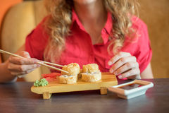 Το κορίτσι τρώει τα ιαπωνικά τρόφιμα κρατά τους ρόλους σουσιών με το ξύλινο chopsti Στοκ εικόνα με δικαίωμα ελεύθερης χρήσης