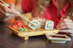 Το κορίτσι τρώει τα ιαπωνικά τρόφιμα κρατά τους ρόλους σουσιών με ξύλινα chopsticks και το moka αυτοί στη σάλτσα σόγιας Στοκ φωτογραφία με δικαίωμα ελεύθερης χρήσης