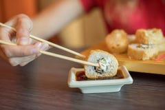Το κορίτσι τρώει τα ιαπωνικά τρόφιμα κρατά τους ρόλους σουσιών με ξύλινα chopsticks και το moka αυτοί στη σάλτσα σόγιας Στοκ Εικόνες