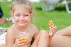 Το κορίτσι τρώει τα μπισκότα, πίνει το χυμό από το πλαστικό μίας χρήσης φλυτζάνι και το χαμόγελο εξέτασε το πλαίσιο Στοκ εικόνα με δικαίωμα ελεύθερης χρήσης