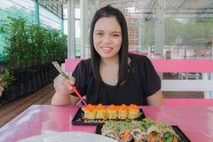 Το κορίτσι τρώει τα σούσια Στοκ εικόνα με δικαίωμα ελεύθερης χρήσης