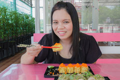 Το κορίτσι τρώει τα σούσια Στοκ Εικόνες