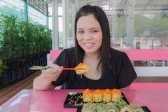 Το κορίτσι τρώει τα σούσια Στοκ φωτογραφία με δικαίωμα ελεύθερης χρήσης