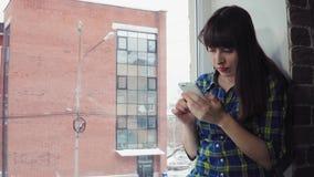 Το κορίτσι τρώει τα στιγμιαία νουντλς καθμένος σε ένα windowsill ενάντια σε ένα κτήριο τούβλου φιλμ μικρού μήκους