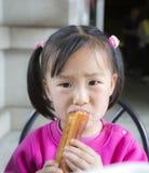 Το κορίτσι τρώει τα τσιγαρισμένα ραβδιά Κίνα ζύμης Στοκ Φωτογραφίες