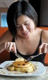 Το κορίτσι τρώει την τηγανίτα μήλων στοκ εικόνες