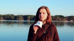 Το κορίτσι τρώει τη σοκολάτα στον ποταμό με τη διασκέδαση απόθεμα βίντεο