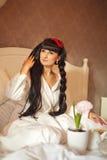 Το κορίτσι τρώει το πρόγευμα στο κρεβάτι παλαιά επιχειρησιακού καφέ συμβάσεων διαμορφωμένη φλυτζάνι φρέσκια γραφομηχανή σκηνής πε Στοκ φωτογραφία με δικαίωμα ελεύθερης χρήσης
