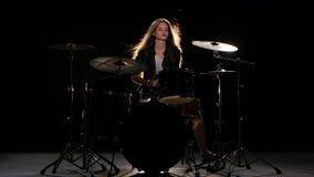 Το κορίτσι τυμπανιστών αρχίζει την ενεργητική μουσική, χαμογελά Μαύρη ανασκόπηση απόθεμα βίντεο