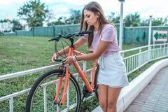 Το κορίτσι υπερασπίζει το ποδήλατό της στο πάρκο το καλοκαίρι Αφαιρεί από το χώρο στάθμευσης, χρησιμοποιεί μια προστατευτική αλυσ στοκ φωτογραφία