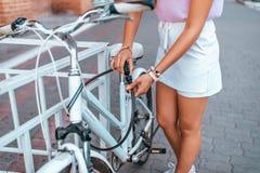 Το κορίτσι υπερασπίζει το ποδήλατό της στο πάρκο το καλοκαίρι Αφαιρεί από το χώρο στάθμευσης, χρησιμοποιεί μια προστατευτική αλυσ στοκ φωτογραφία με δικαίωμα ελεύθερης χρήσης