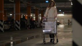Το κορίτσι φέρνει ένα κάρρο αγορών για το χώρο στάθμευσης 4K η αργή Mo απόθεμα βίντεο