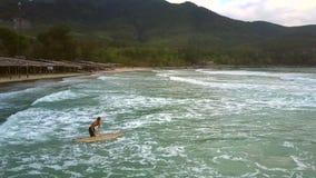 Το κορίτσι φέρνει την ιστιοσανίδα στα foamy ωκεάνια κύματα απόθεμα βίντεο