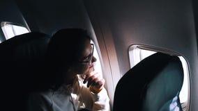 Το κορίτσι φαίνεται έξω το παράθυρο του αεροπλάνου απόθεμα βίντεο
