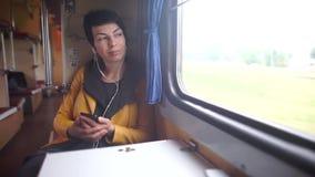 Το κορίτσι φαίνεται έξω το παράθυρο τραίνων, ακούει τη μουσική απόθεμα βίντεο