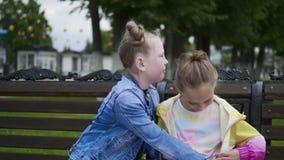 Το κορίτσι φαίνεται κενοί φίλοι τσεπών κάθεται τον πάγκο πάρκων φιλμ μικρού μήκους