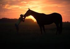 Το κορίτσι φιλά το άλογό της στο ηλιοβασίλεμα στοκ φωτογραφίες