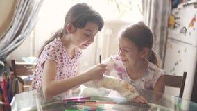 Το κορίτσι φροντίζει την αδελφή της με έναν σπασμένο βραχίονα Το παιδί χρωματίζει έναν επικονιασμένο βραχίονα στη φίλη του απόθεμα βίντεο