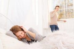 Το κορίτσι φωνάζει την εκμετάλλευση προς το κεφάλι της και ο τύπος μιλά στο τηλέφωνο Στοκ Εικόνες