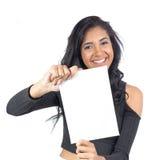 Το κορίτσι χαμογελά και παρουσιάζει άσπρο καρτέλ Θηλυκό πρότυπο που φορά το μαύρο γ Στοκ Εικόνες