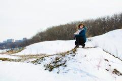 Το κορίτσι το χειμώνα κάθεται σε έναν λόφο έννοια thoughtfulness ή της θλίψης στοκ εικόνα με δικαίωμα ελεύθερης χρήσης