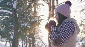Το κορίτσι το χειμώνα ντύνει το καυτό θερμαμένο κρασί κατανάλωσης στο ηλιοβασίλεμα στο χειμερινό δασικό αργό MO φιλμ μικρού μήκους